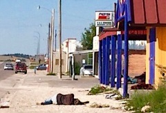 A person lies in the street in Whiteclay