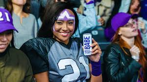 An AB InBev poses with Babe Wine while wearing a football jersey because women deserve to experience alcohol harm too